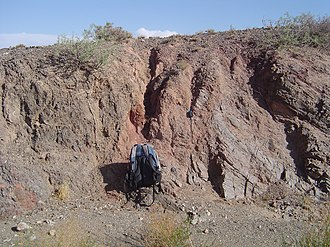 Fault gouge - Salmon-colored fault gouge and associated fault separates two different rock types on the left (dark grey) and right (light grey).  From the Gobi of Mongolia.