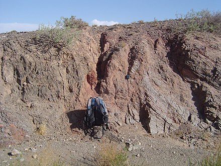 Salmon-colored fault gouge and associated fault separates two different rock types on the left (dark gray) and right (light gray). From the Gobi of Mongolia. FaultGouge.JPG