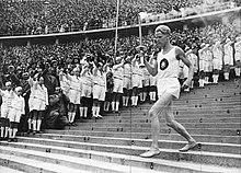 Athlete running down steps holding the Olympic torch
