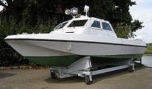 """Blick auf ein kleines stromlinienförmiges Boot, das in einer Wiege aus dem Wasser ruht.  Das Boot ist weiß und grün lackiert, an der Seite ist """"G 718"""" lackiert.  Auf dem Dach seiner offenen Kabine sind zwei Suchscheinwerfer und ein Lautsprecher angebracht."""