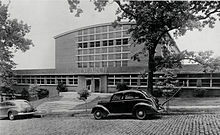 A black-and-white photograph of a one-story building with windows all along it and a multi-story portion of the building set further back from the road. In front of the building, there are two cars parked on a brick-paved road.