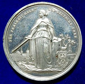 Siege of Strasbourg - German Medal 1870 Siege of Strasbourg, Alsace, in the Franco-Prussian War (obverse). On French arms standing Germania l. holding a sword, the double headed Imperial Eagle on a shield at r. In the background a view of Strasbourg.
