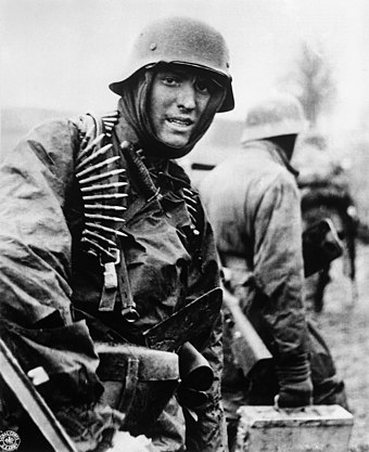A German machine gunner marching through the Ardennes in December 1944 German soldier Ardennes 1944.jpeg