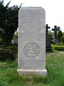 A tall tombstone with an inscription in Latin language and a coat of arms showing a whale and the goddess of fortune