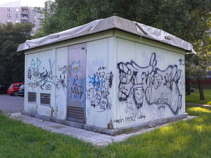 A small power transformer building covered in graffiti.