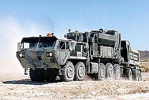 Palletized load system - PLS M1075A0 truck laden with Engineer Mission Modules (EMM); M5 Concrete Mobile Mixer (EMM-CMM) on the truck, and M6 Dump Body (EMM-DB) on the M1076 trailer