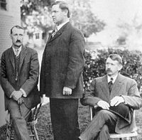 Group portrait of three men, the middle standing in profile.