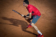 Raonic standing on clay, with his feet wide apart, both hands on his racquet, and looking left. His shadow stretches out sharply to the left.