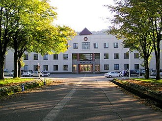 International University of Japan - The tree-lined main entrance and facade of IUJ