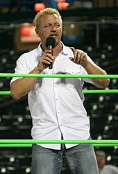 Jeff Jarrett, a blond-haired Caucasian man using a microphone to speak to a crowd