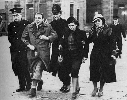 Jewish refugees being marched away by British police at Croydon airport in March 1939. They were put on a flight to Warsaw. Jewish refugees at Croydon airport 1939.jpg