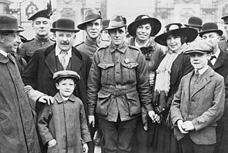 a black and white group photograph of a uniformed Leak with a group of admirers. Leak is holding the hand of a woman standing next to him.