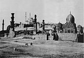 Black and white photograph of a walled city in the desert, showing domes and minarets.