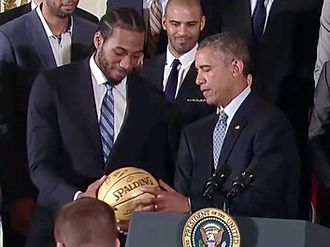 Kawhi Leonard - Leonard handing a signed ball to President Barack Obama at a White House ceremony honoring the Spurs team that won the 2014 NBA Championship
