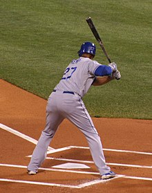"A man stands in a batter's box hunched over home plate. He is wearing a gray baseball uniform that reads ""Kemp"" and ""27"" on the back in blue block lettering and a blue batting helmet."