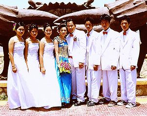 Groomsman - Three groomsmen stand to the left of the groom and three bridesmaids stand to the right of the bride in this wedding in Kep, Cambodia.