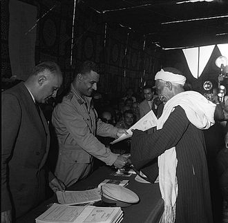History of Egypt under Gamal Abdel Nasser - Nasser handing documents to an Egyptian fellah in a land distribution ceremony in Minya, 1954