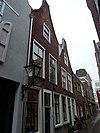 foto van Pand met verdieping onder zadeldak met halsgevel waarin ongedeelde- en 6-ruitsschuifvensters in geprofileerde omlijstingen; 9-ruitsschuifvenster in top