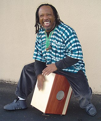 Cajón - Percussionist Leon Mobley playing a modified cajón; traditional cajones have the hole at the back, opposite the tapa