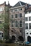 foto van Hoekhuis met overbouwde werf aan de grachtzijde, bestaande uit twee bouwlagen, een kelder en een kap loodrecht op de straat