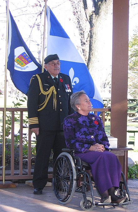 Aide-de-camp Colonel Jean-Claude Cloutier with then-Quebec Lieutenant-Governor Lise Thibault. Lise Thibault-flags.jpg