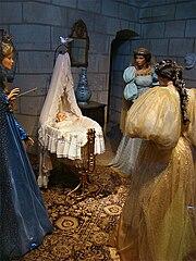Au centre de la photo, un enfant est couché dans un berceau décoré de longs tissus blancs. Trois fées debout autour du berceau observent l'enfant.