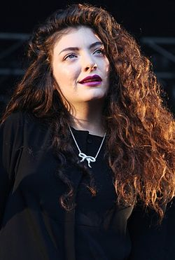 Lorde in a black outfit and smiling
