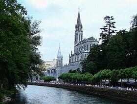Pèlerinage de Lourdes en été avec vue des sanctuaires à droite, du château fort en fond et du gave de Pau.