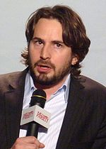 A brunette man is talking while he holds a microphone. He wears a blazer and a blue shirt. He has long hair and a beard.
