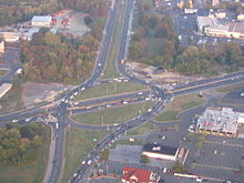 An aerial view of an intersection between two roads, with the top to bottom road splitting into a circular intersection and the left to right road running straight through