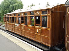 Side view of a varnished wooden railway carriage with doors and windows at regular intervals down the side.