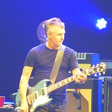 A male electric guitar player, Mike McCready, onstage with an electric guitar plugged into a guitar amplifier.
