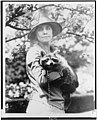Mrs. Calvin Coolidge, half-length portrait, standing, facing front, holding her pet raccoon Rebecca LCCN90714615.jpg