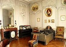 salle couverte de boiseries blanches, avec contre les murs, une cheminée, une vitrine et un lit surmonté d'un portrait. Trois fauteuils sont disposés au centre de la pièce