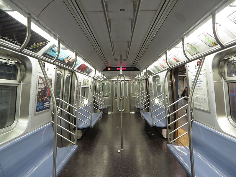 An empty train cart with the the Ads in the ceiling corners and empty wall space