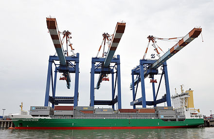 Three pier-side gantry cranes tower over a container ship. - Container ship