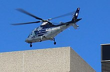 Blue sky, silver helicopter about to land on a stone or concrete building