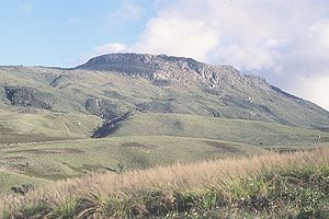 Mount Nyangani - Mount Nyangani from the west. The falls in the middle ground are on the upper Nyamuziwa River and the Tourist Path ascends to their right. The start of the Tourist Path is in the lower right of the picture. The route from the Mountain Club of Zimbabwe hut is on the far side of the skyline ridge on the left of the picture.