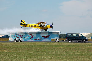 Landing - An unusual landing; a Piper J3C-65 Cub lands on a trailer as part of an airshow.