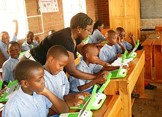 Children in a Rwandan primary school, using laptops supplied by the One Laptop Per Child program OLPC classroom teaching.JPG