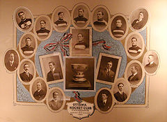 "A montage of photographs of the hockey players and team executives surrounding a photograph of the Stanley Cup trophy, with a caption below of ""Ottawa Hockey Club, Champions and Stanley Cup holders 1909"""