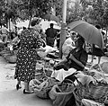 Oudere marktvrouw verkoopt kippen en eieren, zittende onder een paraplu, Bestanddeelnr 254-0780.jpg