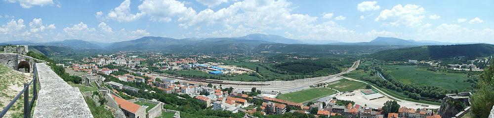 """Панорама Книна сликана са книнске тврђаве. Лијево се налази насеље """"Синобадова главица"""", у средини је комплекс фабрике """"Твик"""". Ток ријеке Крке и стадион ФК Динаре приказани су десно."""