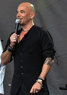 Obispo performing on stage in Paris on Bastille Day 2011