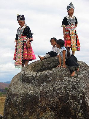 Plain of Jars - Hmong girls climbing on one of the jars at Site 1
