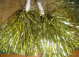 Pom-pom tufts or bunches of ribbon, velvet, or thread, worn in the hair, on a cap, or dress, or similar bunches of streamers used in cheerleading