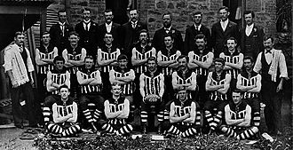 "Port Adelaide Football Club - Left: Port Adelaide adopted the black and white ""Wharf Pylon"" guernsey and the Magpie emblem in 1902. Right: Port Adelaide's 1903 premiership team were the first to win a Grand Final in the ""Wharf Pylon"" guernsey."