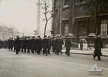 Black-and-white photo of a large group of men wearing military uniforms marching in formation along a city street