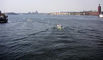 Venstre billede:   Vy over Ridderfærden mod øst fra Västerbron.   Til venstre ligger Kungsholmen, lige frem ses Stockholms Stadshus og til højre derom Riddersholmen.   I forgrunden stævner dampfartøjet S/S Drottningholm ind mod Stadshuskajen.   Højre billede:   Vy mod vest fra Centralbron med fritidsbåde som lige efterlod Slussen, langs til højre ses Stockholms Stadshus og i baggrunden skimter Västerbron.