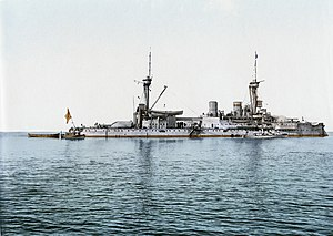 A large gray battleship with two tall masts sits idly in calm waters. Three small boats are tied alongside.